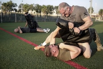 Chef Robert Irvine wrestles with Marine Cpl. Matthew Heldt during a physical training event at Naval Air Station Sigonella, Italy, July 28, 2016. Marines completed a circuit course, which included upper and lower body workouts, and laps around the baseball field, with the celebrity chef. Marine Corps photo by Cpl. Alexander Mitchell