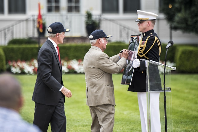 Navy Secretary Ray Mabus, left, looks on as retired Marine Corps Col. Harvey Barnum, Vietnam War Medal of Honor recipient, signs a poster of the USS Harvey C. Barnum Jr., the Navy ship named after him, during a ceremony at Marine Barracks Washington, D.C., July 28, 2016.  DoD photo by U.S. Army Sgt. James K. McCann