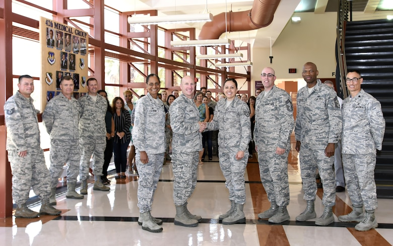 Staff Sgt. Raquel Caramanno, 412th Medical Group, is congratulated by Brig. Gen. Carl Schaefer, 412th Test Wing commander, and the 412th MDG team, during the announcement of her selection as one of the 12 Air Force Outstanding Airmen of the Year.  Pictured, left to right: 412th Medical Group commander, Col. Karen Dean-Cox; Brig. Gen. Carl Schaefer, Staff Sgt. Racquel Caramanno; Chief Master Sgt. Anthony Soto, 412th MDG; Chief Master Sgt. Todd Simmons, 412th TW command chief; and Lt. Col. David Huinker, 412th Medical Support Squadron commander. (U.S. Air Force photo by Dawn Waldman)