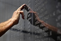 A Korean War veteran looks for the name of a fallen comrade during the National Korean War Veterans Armistice Day ceremony at the New Jersey Korean Veterans War Memorial in Brighton Park, Atlantic City, N.J., July 27, 2016. Air National Guard photo by Tech. Sgt. Matt Hecht