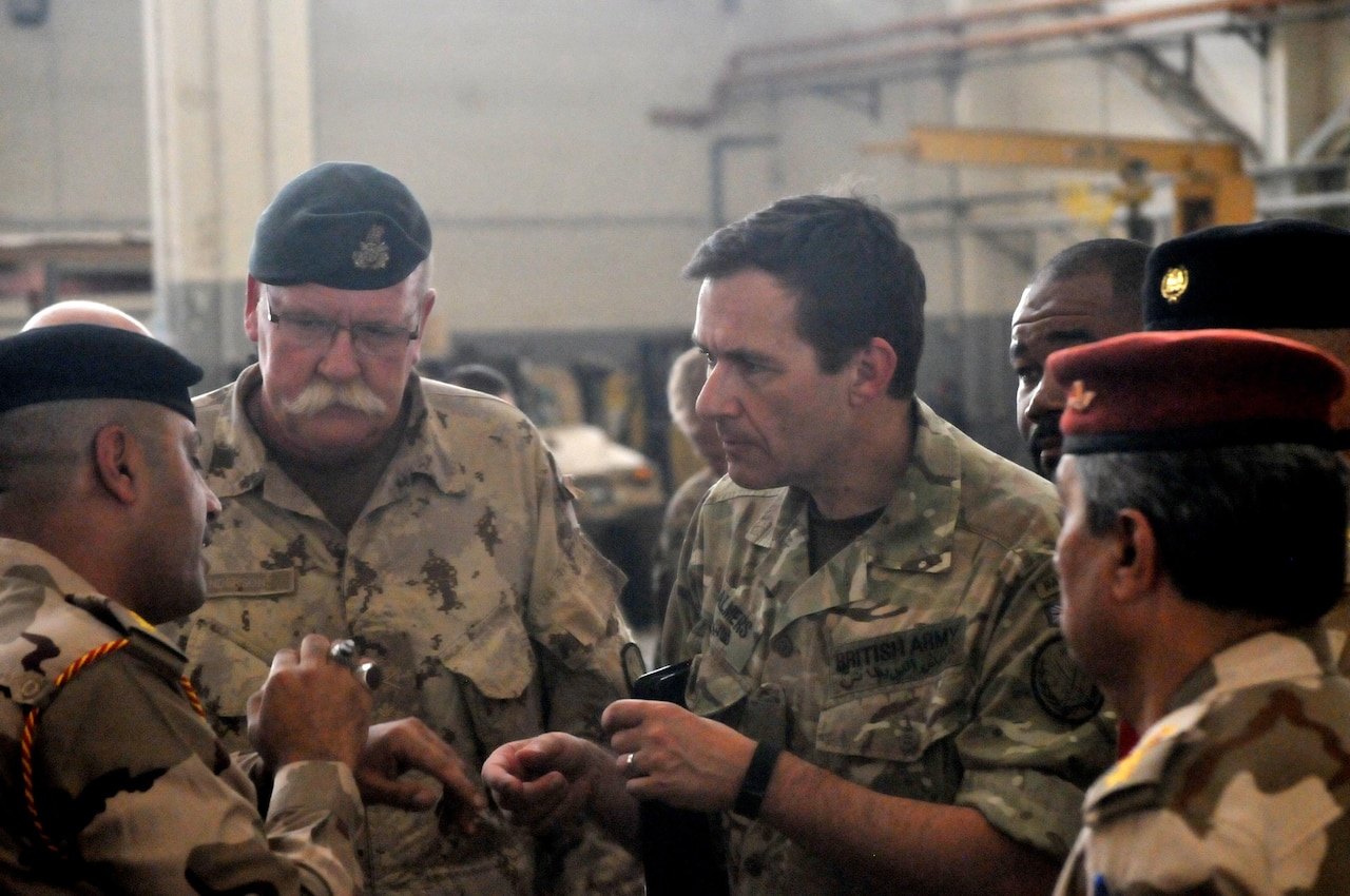 Canadian army Brig. Gen. David Anderson, director of the coalition's ministerial liaison team for Combined Joint Task Force Operation Inherent Resolve, left, and British army Maj. Gen. Doug Chalmers, the coalition's deputy commander of strategy and sustainment, right, speak to the Iraqi leaders of a vehicle maintenance facility during a logistics symposium at Camp Taji, Iraq, July 28, 2016. Army photo by 1st Lt. Daniel Johnson