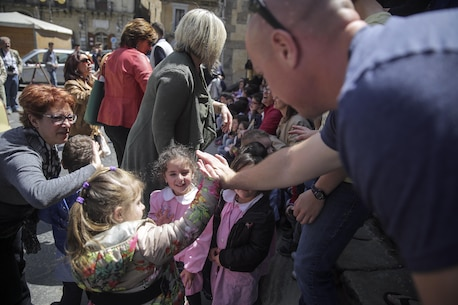 "Sgt. Mateusz Kaczynski, a maintenance management chief with Special Purpose Marine Air-Ground Task Force Crisis Response-Africa, gives a little girl a high-five during a community project in Nicosia, Italy, May 25, 2016.  Students from Instituto di Istruzione Superiore ""Alessandro Volta"" were able to practice their English and share their culture while leading Marines and sailors on a tour around Nicosia. (U.S. Marine Corps photo by Cpl. Alexander Mitchell/released)"