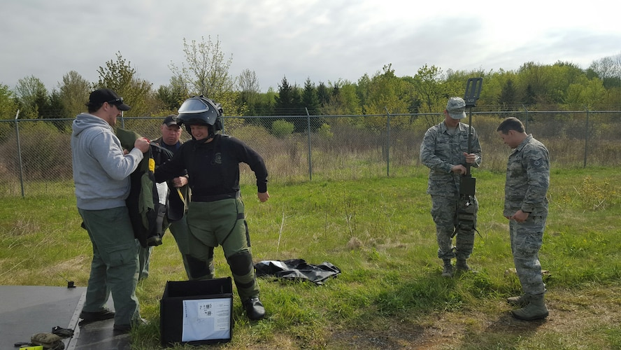 Erie County Bomb Squad members outfit Bomb Squad Commander Daniel Walczak in an Explosive Ordnance Disposal 9 Bomb Suit while SrA Justin Devantier, EOD team member, 914th Civil Engineer Squadron, and Tech. Sgt. Aaron Clark, EOD team leader, 914th Civil Engineer Squadron, prepare a metal detector for operation. The members participated in an inter-agency, improvised explosive device training event known as the Ravens Challenge which was held from May 16-20, 2016 in Oriskany, NY. (U.S. Photo by Tech. Sgt. Adam Clement/released)