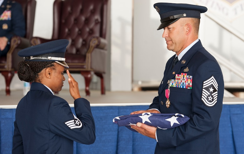 U.S. Air Force Staff Sgt. Latosha Ross, 23d Force Support Squadron base honor guard, salutes the flag after presenting it to U.S. Air Force Chief Master Sgt. David Kelch, 23d Wing command chief, during his retirement ceremony at Moody Air Force Base, Ga., May 26, 2016. Kelch, who has served as the 23d WG's command chief since July of 2014, retired after 29 years and seven months of military service. (U.S. Air Force photo by Andrea Jenkins/Released)