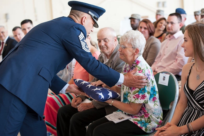 U.S. Air Force Chief Master Sgt. David Kelch, 23d Wing command chief, presents his retirement flag to his mother during his retirement ceremony at Moody Air Force Base, Ga., May 26, 2016. As the command chief, Kelch served as the liaison between the wing commander and the 23d WG's more than 6,000 military and civilian personnel. (U.S. Air Force photo by Andrea Jenkins/Released)