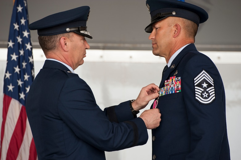 U.S. Air Force Brig. Gen. Chad Franks, senior executive officer to the Air Force vice chief of staff, pins the Legion of Merit medal on Chief Master Sgt. David Kelch, 23d Wing command chief, during a retirement ceremony at Moody Air Force Base, Ga., May 26, 2016. The Legion of Merit is awarded to members of the armed forces who have distinguished themselves by exceptionally meritorious conduct in the performance of outstanding service. (U.S. Air Force photo by Andrea Jenkins/Released)