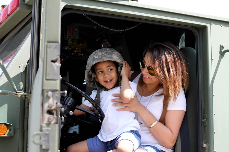 "Ryan Cantres of Kenosha, Wis. tries on the U.S. Army's Advanced Combat Helmet as he sits on his mother's lap and experiences what it's like to ""drive"" a military fire truck during the 2016 Armed Forces Day celebration at the Milwaukee Harley-Davidson Museum, May 21, 2016.  Major Harold Aprill, Executive Officer of the 3rd Battalion, 399th Regiment and a member of  the Milwaukee Armed Services Committee, helped organize the event which capped off an entire week of activities for Milwaukee's Armed Forces Week.    Aprill and reservists from the 3/399th, as well as volunteers from the other branches, helped raise military awareness by displaying military vehicles and explaining to civilians their current role in supporting ongoing military efforts around the world. Servicemembers past and present mingled with the crowd throughout the day, a highlight of which was the 13th annual Support the Troops Ride which featured over 300 motorcycle riders."