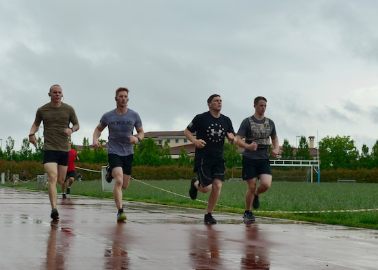 "Participants run around the base track during the Memorial Day ""Murph"" challenge, May 30, 2016, at Aviano Air Base, Italy. The workout, named after fallen U.S. Navy SEAL Lt. Michael Murphy, included a 1-mile run, followed by 100 pull-ups, 200 push-ups, 300 squats, and another 1-mile run to finish. (U.S. Air Force photo by Airman 1st Class Cary Smith/Released)"