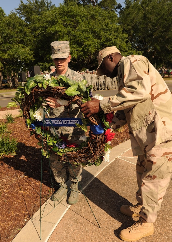 Col. Michele Edmondson, 81st Training Wing commander, and Chief Master Sgt. Harry Hutchinson, 81st TRW command chief, place a wreath on an easel during the 81st TRW Memorial Day Retreat Ceremony May 26, 2016, Keesler Air Force Base, Miss. The ceremony was held in memory of Operation Desert Storm. Attendees were also encouraged to wear uniforms from their past deployments. (U.S. Air Force photo by Kemberly Groue)