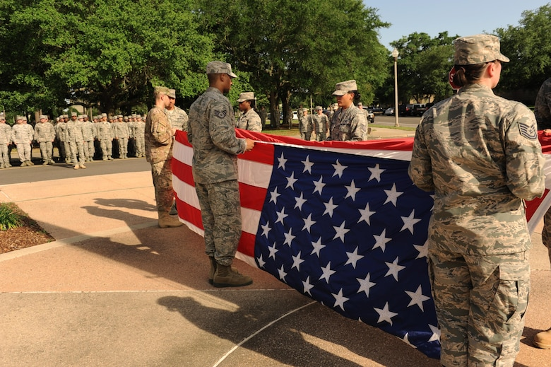 Members of the 334th Training Squadron fold the U.S. flag during the 81st Training Wing Memorial Day Retreat Ceremony May 26, 2016, Keesler Air Force Base, Miss. The ceremony was held in memory of Operation Desert Storm. Attendees were also encouraged to wear uniforms from their past deployments. (U.S. Air Force photo by Kemberly Groue)