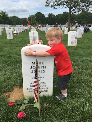 Two-year-old James Jones hugs his father's headstone during a visit to Arlington National Cemetery, Va., May 30, 2016. James and his mother, Sarah Jones, participated in several events with the Tragedy Assistance Program for Survivors during the Memorial Day weekend. (Courtesy photo/Sarah Jones)