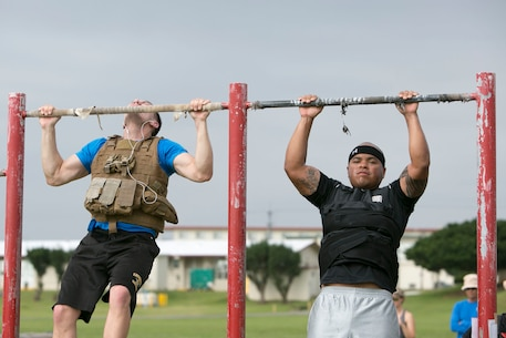 "Lance Cpl. Samuel St. Clair, left, and Sgt. Geirrell Grayer perform pullups while participating in the ""Murph"" Challenge for Memorial Day on Marine Corps Air Station Futenma, Okinawa, Japan. The ""Murph"" Challenge is a workout made to honor Lt. Michael ""Murph"" Murphy, a navy SEAL who died in Afghanistan June 28, 2005, at the age of 29. The challenge consists of a one-mile run, 100 pullups, 200 pushups, 300 squats, and another one-mile run, while wearing a 20 pound vest. St. Clair is a financial management resource analyst with Headquarters and Headquarters Squadron, MCAS Futenma, Marine Corps Installations Pacific. Grayer is a distribution management specialist with Headquarters and Support Battalion, Marine Corps Installations Pacific-Marine Corps Base Camp Butler, Japan. (Marine Corps Photo by Cpl. Douglas Simons/Released)"