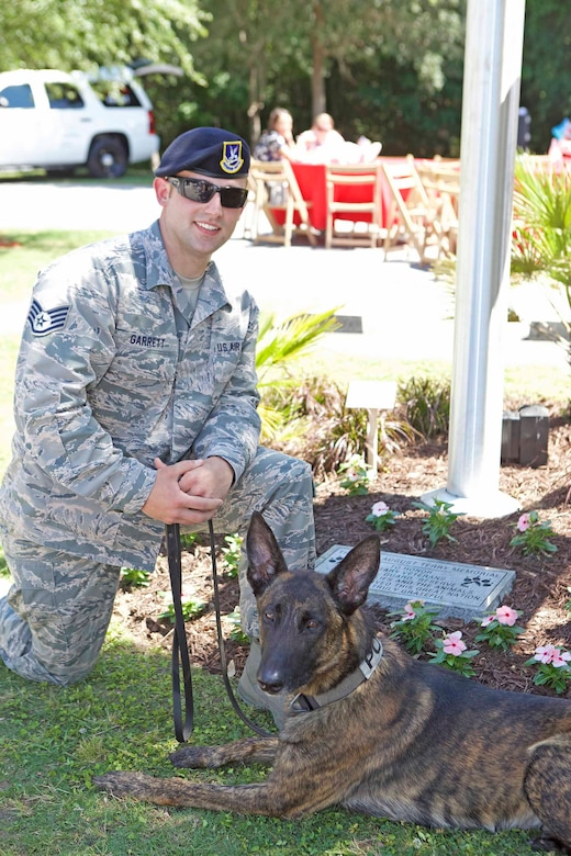 U.S. Air Force Staff Sergeant Jonathan Garrett, Military Working Dog handler, 628th Security Forces Squadron, poses with military working dog Chico in front of the Joan August Terry military memorial on May 20, 2016, at the Charleston Animal Society campus, S.C. The Terry military memorial commemorates the military service of men, women and the animals that served alongside them. (Courtesy photo by Charleston Animal Society)
