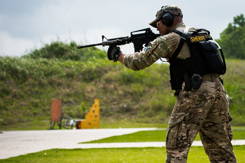 Oklahoma Army National Guard Chief Warrant Officer 2 Tyrie Haught, a Chinook pilot at the 2-149 General Support Aviation Battalion in Lexington, Okla., and also a deputy sheriff for Oklahoma County, fires a weapon during a transition exercise at the Oklahoma County Sheriff's Office Training Center in Oklahoma City, May 26, 2016. Four Will Rogers Air National Guard Base Airmen joined local policing agencies for weapons training, May 24-26. The Oklahoma Country Sheriff's Office led the training to enhance communication and compatibility between various Oklahoma law enforcement groups. (U.S. Air National Guard photo by Senior Airman Tyler Woodward)