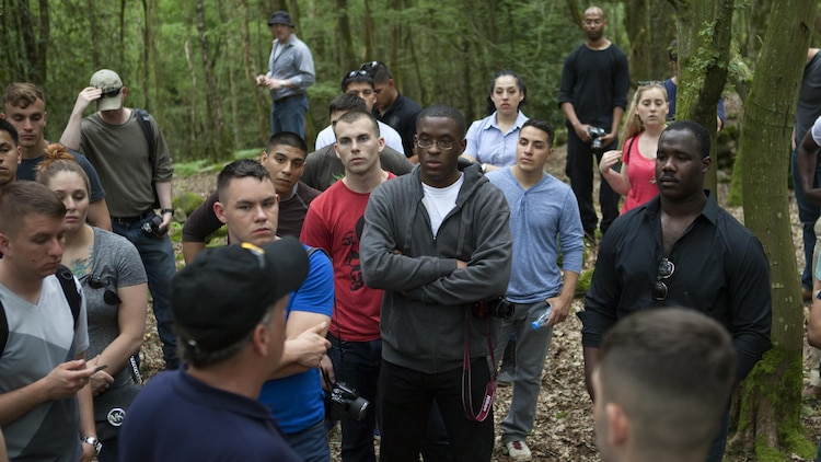 Marines listen to Mr. Ray Shearer, a Marine veteran and director and chairman of American Oversees Memorial Day Association, explain different factors in the Battle of Belleau Wood during World War I, on the battle ground Belleau, France, May 26, 2016. Marines observed trenches, depressions of fighting holes and enemy shelling on the battle ground.