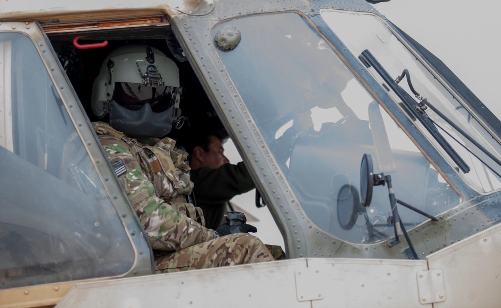 An Afghan Air Force pilot powers down an Mi-17 helicopter as a Train Advise Assist Command-Air Mi-17 Air Advisor looks out a cockpit window after a training mission at Kandahar Airfield, Afghanistan, earlier this ye. Members of the 441st Air Expeditionary Advisory Squadron at KAF worked with AAF pilots on take-off, landing and emergency procedures. (U.S. Air Force Photo by Tech. Sgt. Robert Cloys)