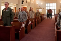 Audience members stand at attention while members of the base honor guard bring forth a wreath of flowers to be laid out during a Memorial Day remembrance ceremony held at the base chapel May 27, 2016, at Incirlik Air Base, Turkey. The ceremony was a time to reflect on those lost during past and current conflicts. (U.S. Air Force photo by Staff Sgt. Jack Sanders/Released)