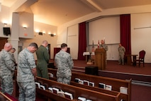 Leadership bows their heads as U.S. Air Force Chaplain (Capt.) David Merrifield, 39th Air Base Wing, gives the invocation during a Memorial Day remembrance ceremony held at the base chapel May 27, 2016 at Incirlik Air Base, Turkey. Merrifield spoke on remembering the shoulders we stand on as we continue today's missions. (U.S. Air Force photo by Staff Sgt. Jack Sanders/Released)