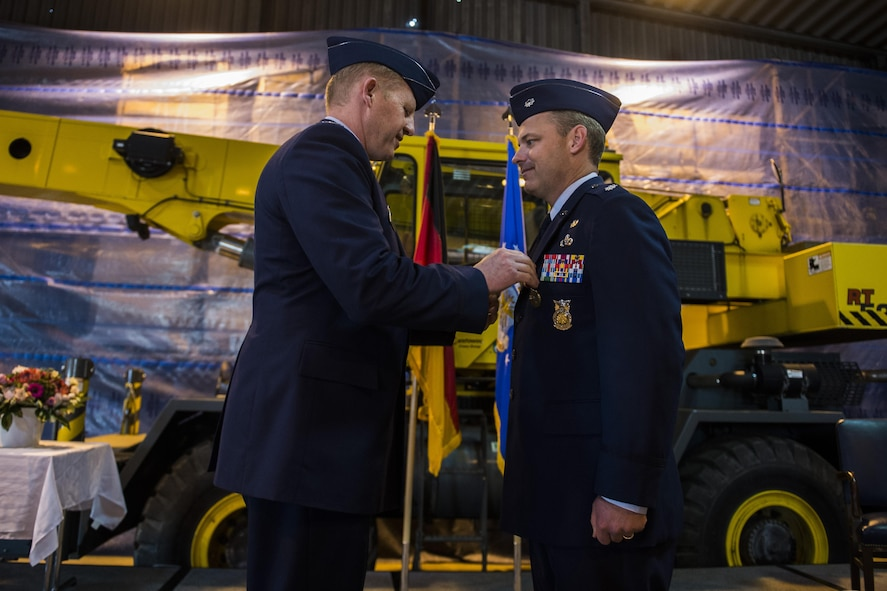 U.S. Air Force Col. Joe McFall, 52nd Fighter Wing commander, left, pins a Meritorious Service Medal on U.S. Air Force Lt. Col. Christopher Meeker, former 52nd Civil Engineer Squadron commander, during the 52nd CES change of command at Spangdahlem Air Base, Germany, June 1, 2016. The Meritorious Service Medal is awarded to members of the Armed Forces of the United States and friendly foreign nations who distinguished themselves by outstanding noncombat meritorious achievement. (U.S. Air Force photo by Senior Airman Luke Kitterman/Released)