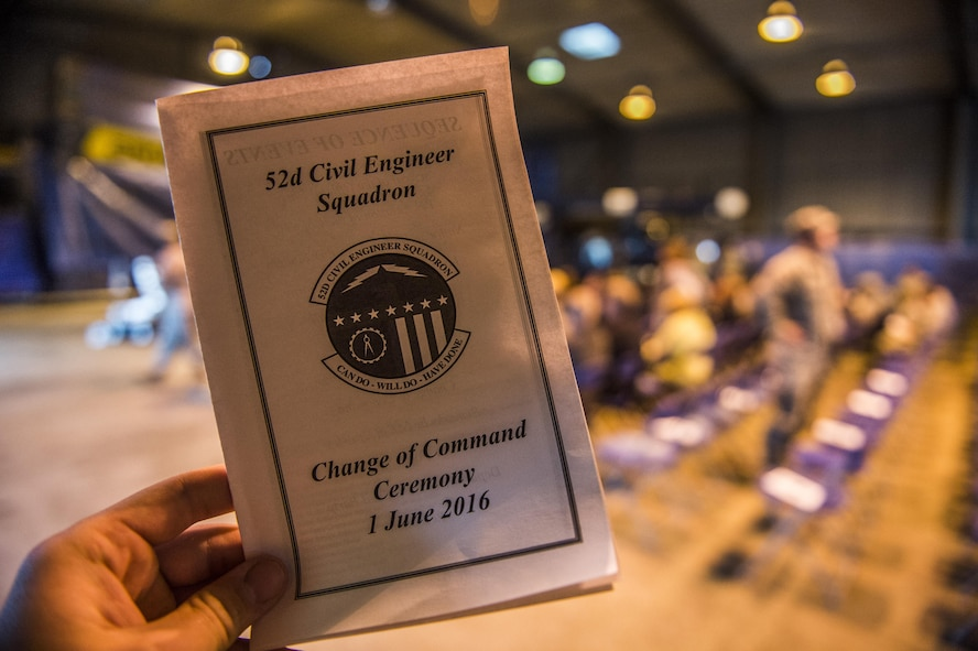 A brochure is held before the start of the 52nd Civil Engineer Squadron change of command ceremony at Spangdahlem Air Base, Germany, June 1, 2016. U.S. Air Force Col. Joe McFall, 52nd Fighter Wing commander, exchanged command of the 52nd CES from U.S. Air Force Lt. Col. Christopher Meeker, former 52nd CES commander, to U.S. Air Force Lt. Col. Ryan Crowley, incoming 52nd CES commander. (U.S. Air Force photo by Senior Airman Luke Kitterman/Released)