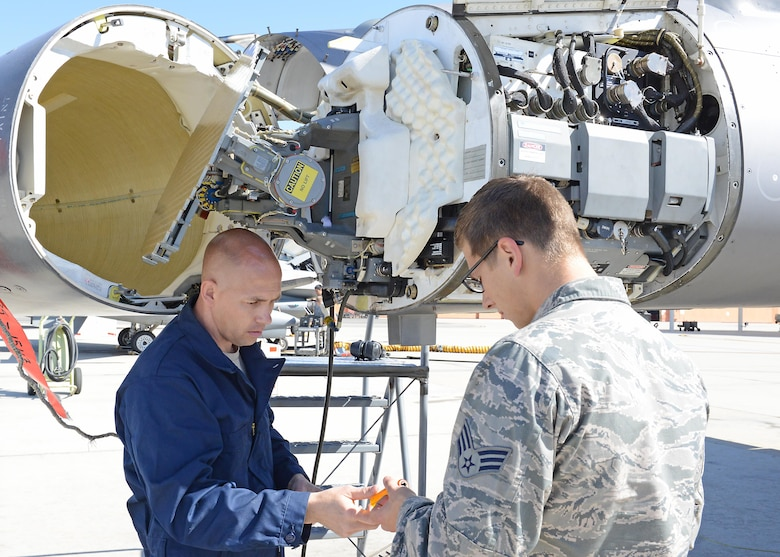 Senior Master Sgt. Samuel Rock, an Air Force Reserve volunteer from Seymour Johnson Air Force Base, N.C., works with Senior Airman Quilan Johansen, of the 412th Aircraft Maintenance Squadron, on an F-16 Fighting Falcon radar waveguide pressurization. Reservists are augmenting F-16 support for KC-46 Pegasus testing at Edwards Air Force Base, Calif. (U.S. Air force photo/Kenji Thuloweit)