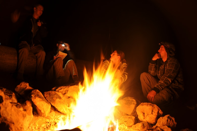 Participants of the U.S. Air Force 50 Summits Challenge converse around a fire at Fort Tuthill County Park Ariz., May 28, 2016. The group of participants consisting of U.S. Airmen, veterans and civilians camped out the night before summiting Humphreys Peak, the highest point in Arizona. (U.S. Air Force photo by Airman 1st Class Ashley N. Steffen/Released)