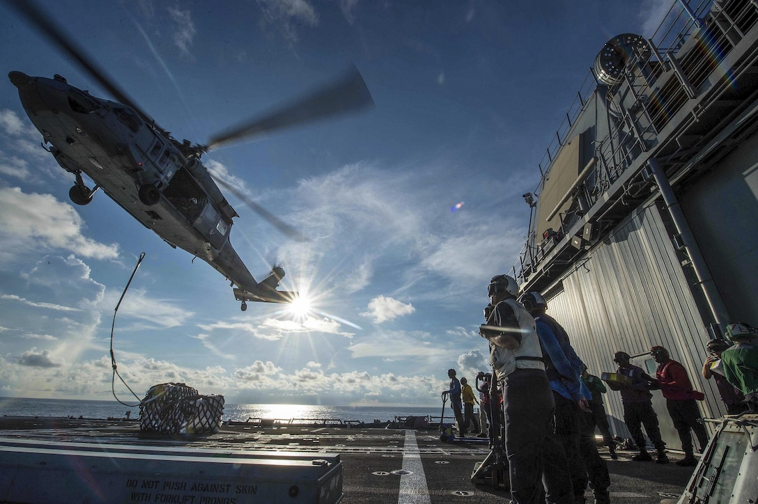 Sailors aboard the USS Mobile Bay receive two of 21 pallets from an MH-60S Seahawk helicopter during a vertical replenishment in the South China Sea, May 29, 2016. The guided-missile cruiser supports security and stability in the Indo-Asia-Pacific region. Navy photo by Petty Officer 2nd Class Ryan J. Batchelder