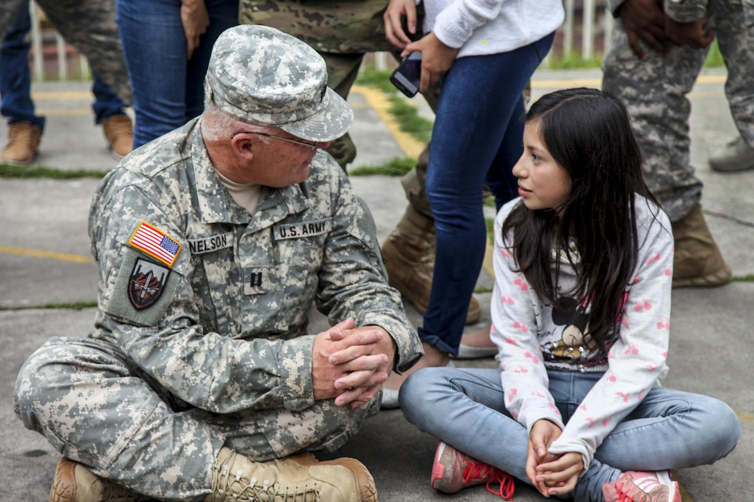 Army Capt. Saint Nelson sits on the ground to speak with a Guatemalan student in San Marcos, Guatemala, June 1, 2016. Task Force Red Wolf and Army South conduct Humanitarian Civil Assistance Training, which includes construction projects, building schools and medical readiness training. Nelson is assigned to the 345th Psychological Operations Company Airborne. Army photo by Spc. Tamara Cummings