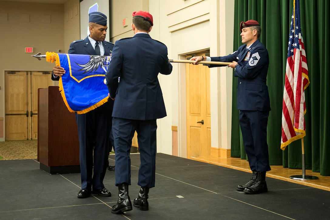 Chief Master Sgt. Ronald Thompson, at right, chief enlisted advisor for the Battlefield Airman Training Group, unfurls the BA TG guidon for Col. Ronald Stenger, incoming commander of the BA TG, left, and Col. Roy Collins, commander of the 37th Training Wing, right, during the group's activation ceremony June 2, 2016, at Joint Base San Antonio-Lackland, Texas. As a result, BA training, which is currently located across eight locations in seven states, will streamline the training pipeline to reduce costs, and lead to improvements and synergies in the process.
