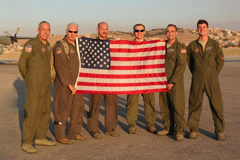 700th Airlift Squadron aircrew members display an American flag that flew on their C-130 flight over Jordan in support of Exercise Eager Lion, May 19, 2016. This year, Eager Lion was a bilateral exercise including the U.S. and Jordanian military forces. (U.S. Air Force photo/Staff Sgt. Alan Abernethy)