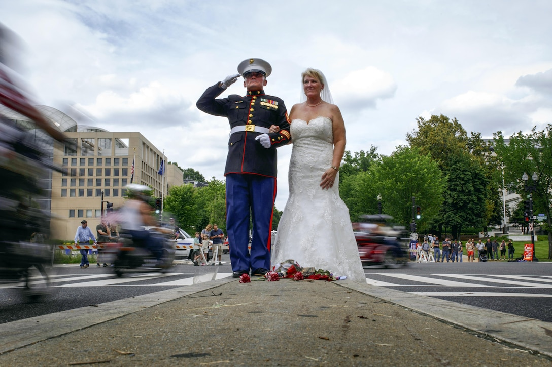 Retired Staff Sgt. Tim Chambers holds a salute for four hours to mark his 15th Rolling Thunder, an annual motorcycle ride, with his bride, Lorraine Chambers, in Washington, D.C., May 29, 2016. Chambers married Lorraine in the same spot where he rendered his salute. The event raises awareness for those missing in action and prisoners of war. Marine Corps photo by Lance Cpl. Molly Hampton