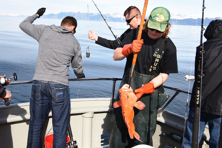 Volunteer deck hand Kyle Collins prepares a yellow-eyed rockfish for the fish box as military anglers wet their lines in the 10th Annual Armed Services Combat Fishing Tournament May 26 aboard the Seward Military Resort boat, Snowbird. The tournament, hosted by the city of Seward and the Armed Services YMCA, gave more than 200 military anglers stationed in Alaska a free day of halibut fishing to thank them for their service. (U.S. Army photo by John Pennell)