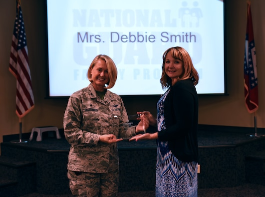 Debbie Smith receives the 2016 Arkansas National Guard Volunteer of the Year Award from Col. Bobbi Doorenbos, 188th Wing commander, May 15, 2016, during commander's call at Ebbing Air National Guard Base, Fort Smith, Ark. Smith has been a key volunteer for the 188th since 2012 and was named the 188th's Outstanding Volunteer in 2013 and 2015. Smith also won the National Region Six Volunteer of the Year Award. (U.S. Air National Guard photo by Senior Airman Cody Martin/Released)