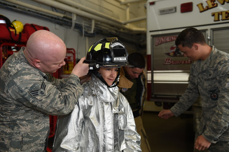 Nicholas Duffy, Pilot for a Day, tries on a fire fighter helmet at the McChord Field Fire Station at Joint Base Lewis-McChord, Wash., May 26, 2016. The Duffy brothers are the 4th Airlift Squadron's newest Pilots for a Day and spent a day visiting units on base and talking to Airmen. (U.S. Air Force photo/Staff Sgt. Naomi Shipley)
