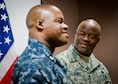 Master Sgt. Antone Scott, 96th Maintenance Group, stands beside his twin brother, Lt. Cmdr. Anthony Scott, after his oath of enlistment ceremony May 31 at Eglin Air Force Base, Fla.  This is the second time the twins participated in an enlistment ceremony together.  The first time was in 2013.  This enlistment allows Antone to put on his senior master sergeant stripe.  (U.S. Air Force photo/Samuel King Jr.)
