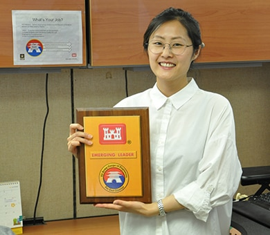 Ka Young Shim holds a plaque showing her status as the Far East District's new Emerging Leader.