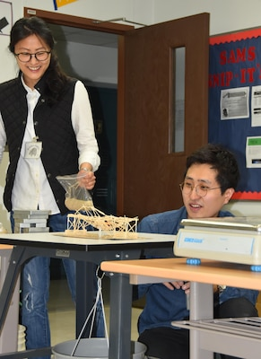 "Ka Young Shim, an Architect in Engineering Division's Design Branch, was recently selected as the Far East District's ""Emerging Leader."" The emerging leader program is a U.S. Army Corps of Engineers initiative geared to develop employees' leadership skills and future development. Here, Shim works with another FED employee at a STEM event, testing the load-bearing capacity of toothpick bridges designed and built by students at Seoul American Middle School."