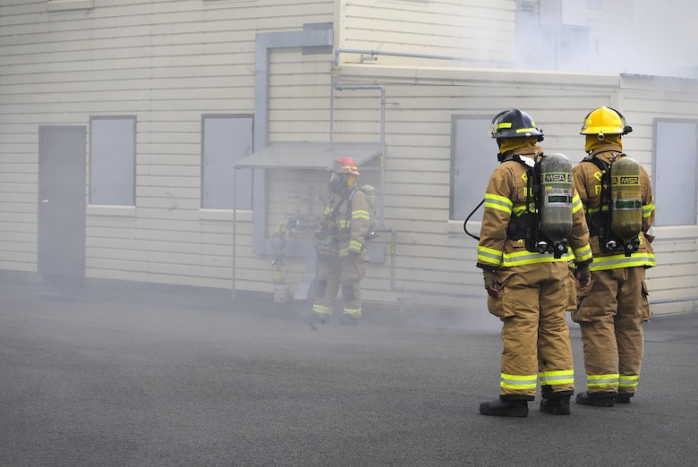 Airmen from the 86th Civil Engineer Squadron prepare to enter a simulated burning house during a biannual-training exercise June 2, 2016, at Ramstein Air Base, Germany. The 86th CES Airmen provide fire emergency services to Ramstein Air Base, Vogelweh Military Complex, Rhine Ordinance Barracks and Landstuhl military sites (U.S. Air Force photo/Senior Airman Larissa Greatwood)