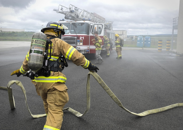 Airmen from the 86th Civil Engineer Squadron prepare fire hoses during a biannual-training exercise June 2, 2016, at Ramstein Air Base, Germany. Though Airmen are required to conduct each type of training annually, they continuously work to maintain and expand their skillsets. (Senior Airman Larissa Greatwood)