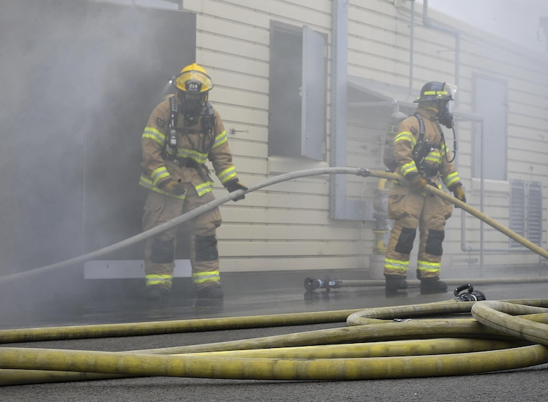Airmen from the 86th Civil Engineer Squadron guide a firehose into a simulated burning house during a biannual training exercise June 2, 2016, at Ramstein Air Base, Germany. The Airmen constantly train for competency in their skillsets as well as expanding their training and knowledge. (U.S. Air Force photo/Senior Airman Larissa Greatwood)