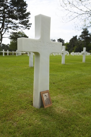 The photo of Army Pfc. Alfred H. Carlton rests against his headstone in the Normandy American Cemetery in Colleville sur Mer, France, May 25, 2016. Cpl. Joshua Bettis, an outbound clerk at distribution management office, Henderson Hall, was the first person in his family to visit this grave of his great, great uncle.