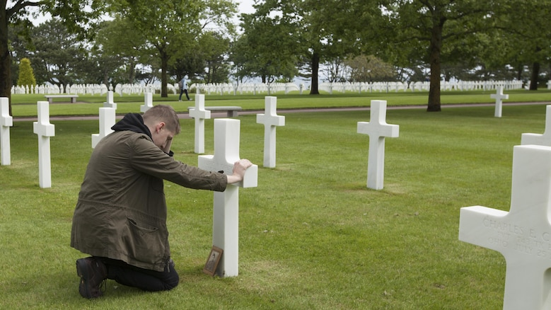Cpl. Joshua Bettis, an outbound clerk at distribution management office, Henderson Hall, kneels at the grave of his great-great-uncle Army Pfc. Alfred H. Carlton at the Normandy American Cemetery in Colleville sur Mer, France, May 25, 2016. Carlton died from wounds in the D-Day invasion during World War II in Normandy, France. Bettis was the first person in his family to visit the gravesite.