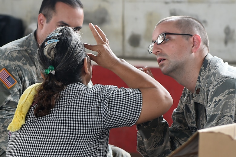 Maj. Robert Carlsen, right, the 22nd Aerospace Medical Squadron optometry flight commander, examines the eyes of Isabella Morales at the medical readiness training exercise in La Blanca, Guatemala, May 28, 2016, during exercise Beyond the Horizon 2016. Carlsen ensured that Morales did not have any visible damage to her eyes before performing an eye examination. (U.S. Air Force photo/Senior Airman Dillon Davis)