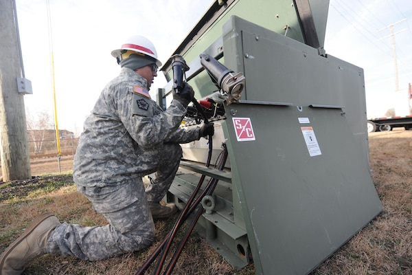 Spec. Arnold Wicker of the 249th Engineer Battalion (Prime Power) attaches cables to a power transfer box while installing generators at a Carteret, New Jersey power plant that lost power during Hurricane Sandy Nov. 6, 2012. DLA provided additional power generators to the Federal Emergency Management Agency to aid in the recovery effort.