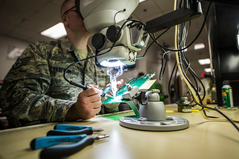 Staff Sgt. Kyle Eilefson, an Air Force Repair Enhancement Program technician with the 1st Special Operations Maintenance Squadron, solders resistors on a circuit board at Hurlburt Field, Fla., May 24, 2016. The circuit board is part of the power supply for the approach lighting system on the Hurlburt Field runway. (U.S. Air Force photo by Senior Airman Krystal M. Garrett)