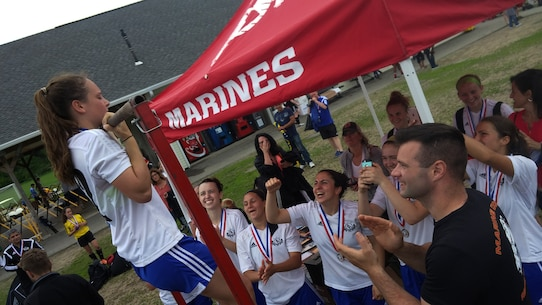 Staff Sgt. Shane Howard, canvassing recruiter with Recruiting Substation Worcester, Massachusetts, cheers on a soccer player conducting the flexed-arm hang with the rest of her team following their bracket win at the Global Premier Soccer Memorial Day Tournament, May 30, 2016.