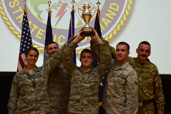 Members of the 460th Space Wing hold up the Omaha Trophy during a commander's call April 15, 2016, on Buckley Air Force Base, Colo. The wing won the trophy for the first time by executing more than 8,000 error-free operation hours and providing critical missile warning and missile defense. (U.S. Air Force photo by Airman 1st Class Gabrielle Spradling/Released)