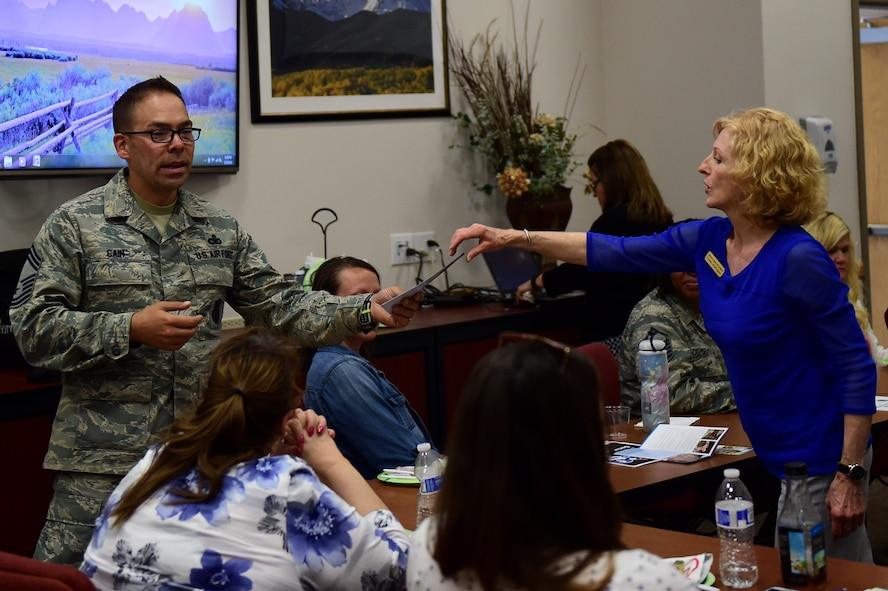 Cindy Darugna, Buckley Airman & Family Readiness Center Military Family Life counselor, provides Chief Master Sgt. Brian Cain, 460th Security Forces manager, with Military Family Life Counseling literature May 19, 2016, during a Hearts Apart event on Buckley Air Force Base, Colo. MFLC works with families, individuals, couples and children to provide non-medical problem identification and counseling services. (U.S. Air Force photo by Airman 1st Class Gabrielle Spradling/Released)
