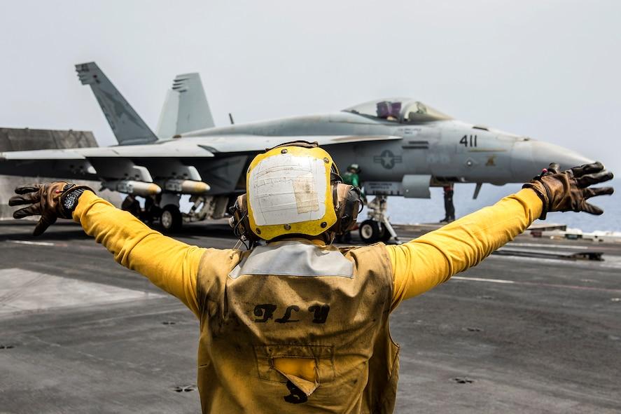 Navy Petty Officer 3rd Class Raimon Hubbard directs an F/A-18E Super Hornet on the flight deck of the aircraft carrier USS Harry S. Truman