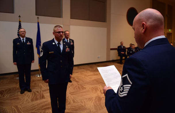 Master Sgt. David Kechter, 460th Security Forces Squadron standards and evaluation superintendent , reads the senior noncommissioned officer creed May 31, 2016, to Buckley Air Force Base's newest master sergeant, Master Sgt. Travis Rathje, 460th Space Communications Squadron plans and resources section chief, during the May promotion ceremony at the Leadership Development Center on Buckley AFB, Colo. The creed outlined what a senior NCO is and what is expected of them. (U.S. Air Force photo by Airman 1st Class Gabrielle Spradling/Released)